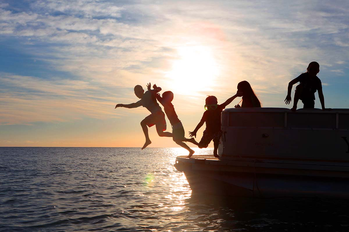 Kids playing on a boat at sunset in Barbados